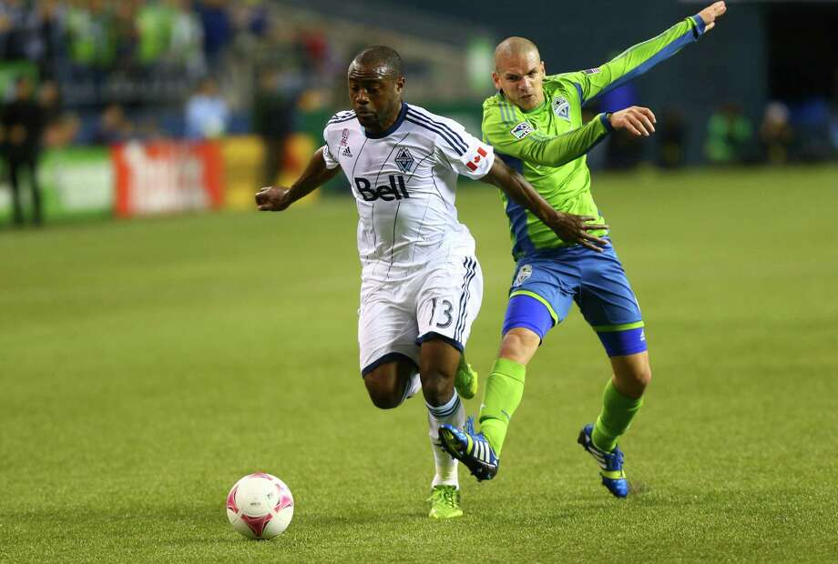 Seattle Sounders player Osvaldo Alonso and Vancouver Whitecaps player Nigel Reo-Coker battle for control of the ball in the first half of a match Wednesday, October 9, 2013 at CenturyLink Field in Seattle. Photo: JOSHUA TRUJILLO, SEATTLEPI.COM / SEATTLEPI.COM