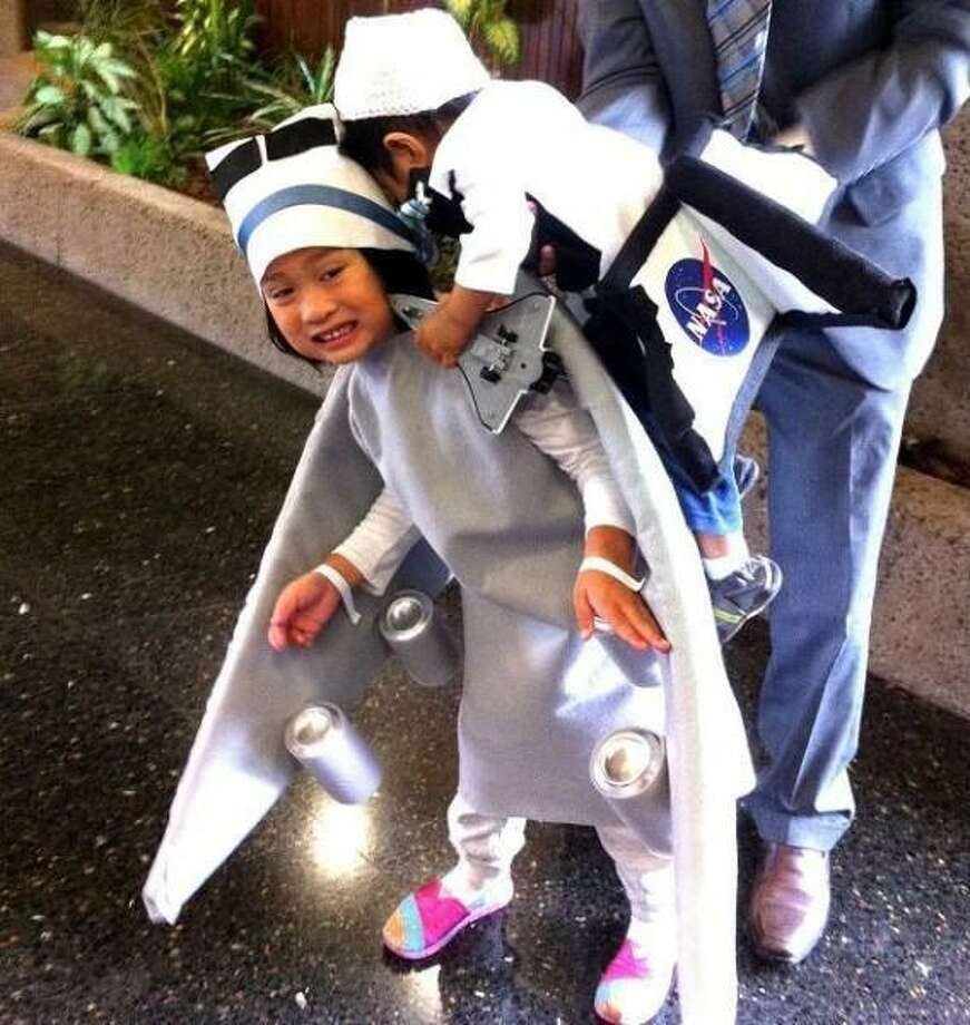 SPACE SHUTTLE ENDEAVOR (2012):  Longtime reader Rhean submitted this topical costume, which included her 4-year-old daughter as the jet that gave the Space Shuttle Endeavor (her 1-year-old brother)  victory tour ride across the state. There are great details here, but the girl's smile is the best.