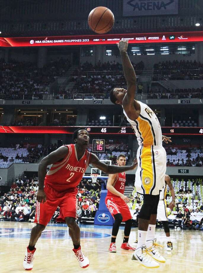 Paul George of the Pacers knocks down a high pass as Rockets point guard Patrick Beverley looks on. Photo: Mike Young, Getty Images