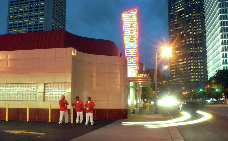 ** ADVANCE FOR WEEKEND EDITIONS, JULY 26-27 **A car pulls into the parking lot as car hops, from left, Blast Collins, Edgar Rogers, and William Robinson wait to deliver curbside service at the Varsity in Atlanta, Monday evening July 21, 2003. The restaurant situated near Georgia Tech has long been an Atlanta landmark and is celebrating its seventy fifth anniversary this year. (AP Photo/John Amis) Photo: JOHN AMIS, AP / AP