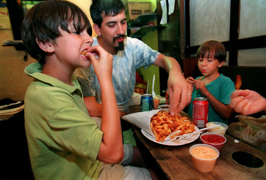 A hearty helping of Belgian frites make a meal at a Pommes Frites  shop in Manhattan. Jacob Nelsen Epstein, 7, left, his father David,  center, and brother Dylan, 5, laid out a variety of sauces for dipping.  (AP Photo/Kathy Willens)  FRENCH OR BELGIAN FRIES. FRY Photo: KATHY WILLENS, AP / AP