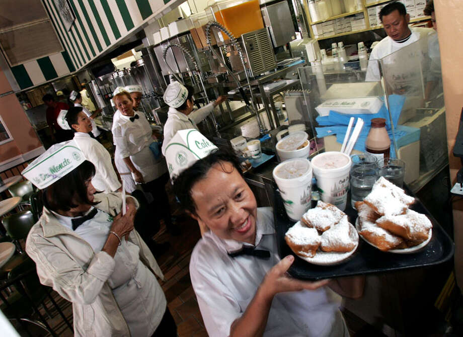 Waitress Dung Hguyen carries a tray of Cafe Du Monde's famous doughnuts, Beignets, early Wednesday morning, Oct. 19, 2005 at the French Quarter cafe's reopening in New Orleans, La. (AP Photo/Mel Evans) Photo: MEL EVANS, AP / AP