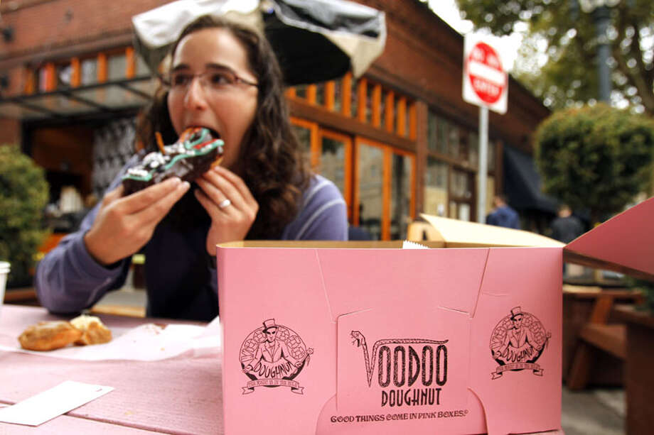 Jennie Myren, who is from Iowa and spending her honeymoon in Portland, enjoys the signature doughnut shaped like a voodoo doll with a pretzel stick stake through its' heart outside the famous Voodoo Doughnuts shop in downtown Portland, Ore., Wednesday, Sept. 19, 2012. Researchers at Portland State University found that the Portland atmosphere and culture is a magnet for the young and college educated, even though a disproportionate share of them are working in part-time jobs or positions that don't require a college degree. (AP Photo/Don Ryan) Photo: Don Ryan, Associated Press / AP