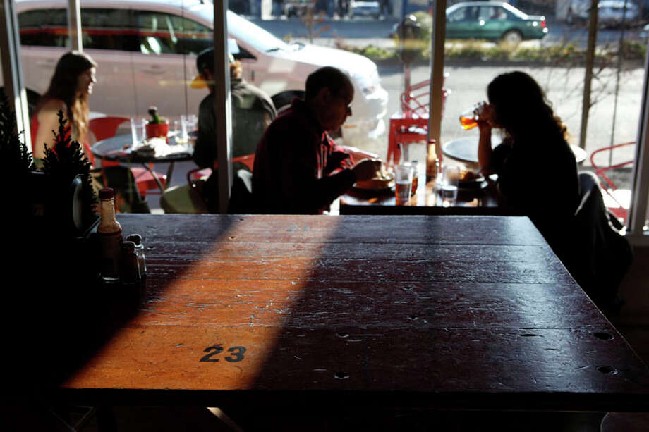 Patrons dine on dishes of mac and cheese and sip on beer while sitting at a table made of former bleachers from Redwood City High School at Homeroom restaurant on Wednesday, December 21, 2011 in Oakland, Calif. Photo: Beck Diefenbach, Special To The Chronicle / ONLINE_YES