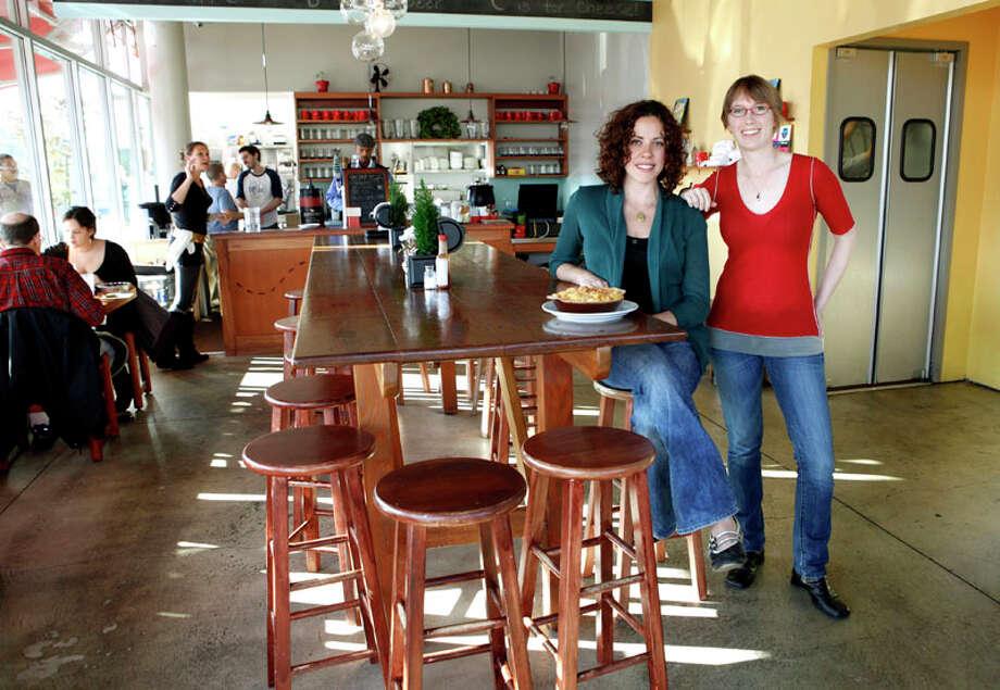 Co-owners Erin Wade (right) and Allison Arevalo sit with a dish of Spicy Mac at a communal seating table made of old high school bleachers at Homeroom restaurant on Wednesday, December 21, 2011 in Oakland, Calif. Photo: Beck Diefenbach, Special To The Chronicle / ONLINE_YES