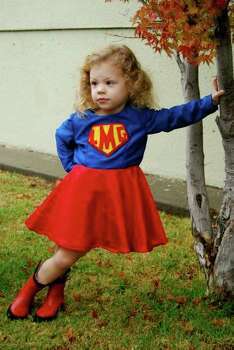 "SUPERGIRL (2008): This Supergirl costume made for 2-year-old Lauren was a hit. Said mother Lisa: ""Believe it or not, we did not pose her for this photo — she was waiting for her preschool's Halloween parade to begin and got a little impatient."" Photo: Courtesy Lisa Buccino"