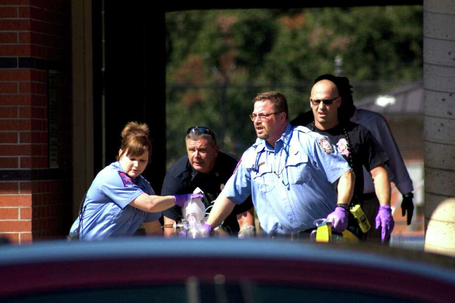 Emergency responders take an adult man out of Alice Keith Park pool Thursday morning. Police weren't sure how the man and a little girl got access to the facility, which has been closed since September. Photo: Tim Monzingo