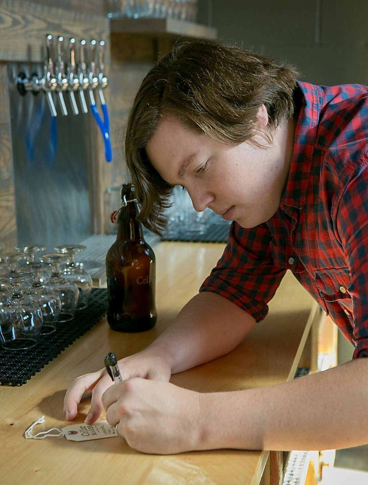 Brewer Connor Casey fills out a tag for a growler at his new brew pub, Cellarmaker Brewery in San Francisco, Calif., on Friday, October 4th, 2013.