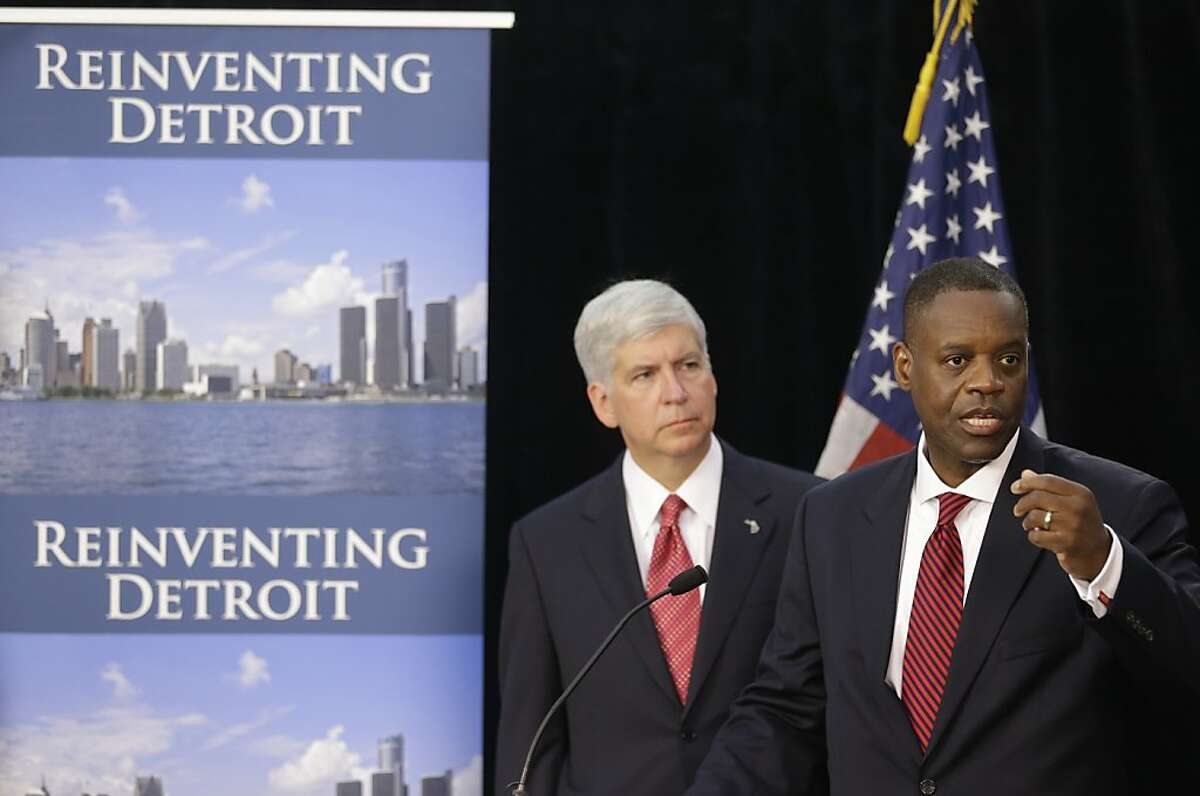 FILE - In this July 19, 2013, file photo, state-appointed emergency manager Kevyn Orr, right, and Michigan Gov. Rick Snyder, address reporters during a news conference in Detroit after Orr asked a federal judge for bankruptcy protection. While no other city is expected to join Detroit in bankruptcy court anytime soon, Detroit's bankruptcy is casting a shadow over a long list of cities across the U.S. and giving mayors new urgency in the search for solutions to the greatest challenge to face America's cities in a generation. (AP Photo/Carlos Osorio, File)