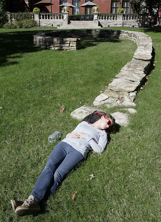 Snoozing sophomore Rachel Bryant forms the dot at the bottom of a stone wall question mark at the Kansas City Art 