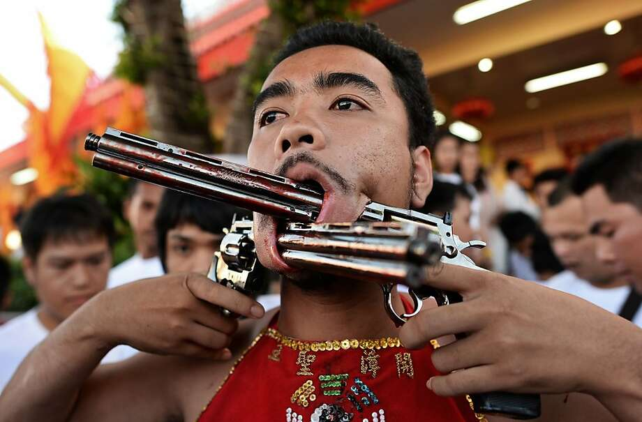 Shooting from the lip:During the Vegetarian Festival in the Phuket, Thailand, devotees pierce themselves with all sorts of objects and 