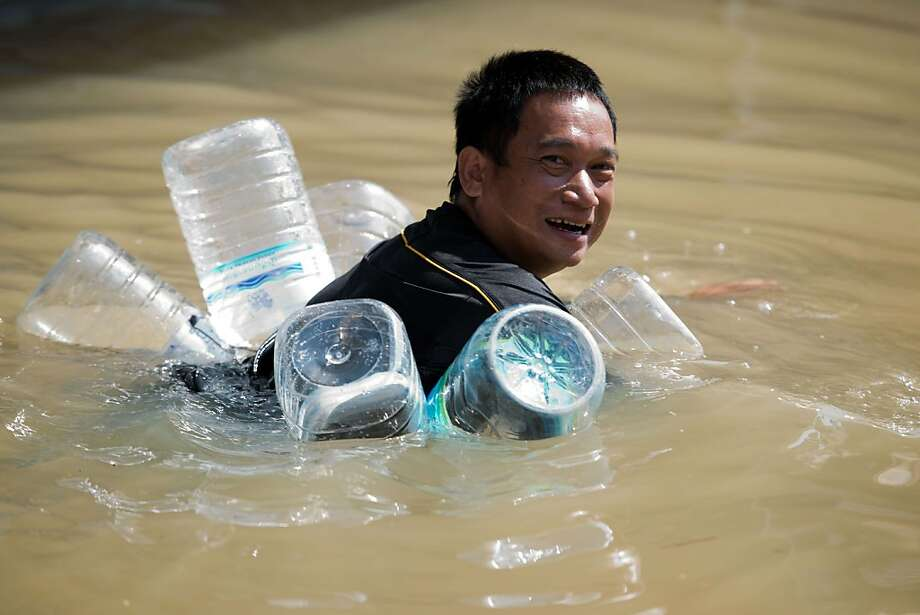 Buoyed by a plastic bottles, a villager swims in floodwaters in Kabin Buri, Thailand. Twenty-seven provinces in Thailand remain flooded following weeks of rain. Photo: Nicolas Asfouri, AFP/Getty Images