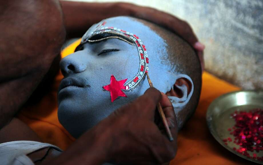 Star treatment: A Hindu devotee applies sequins and makeup to the face of a boy portraying the Hindu god Rama ahead 