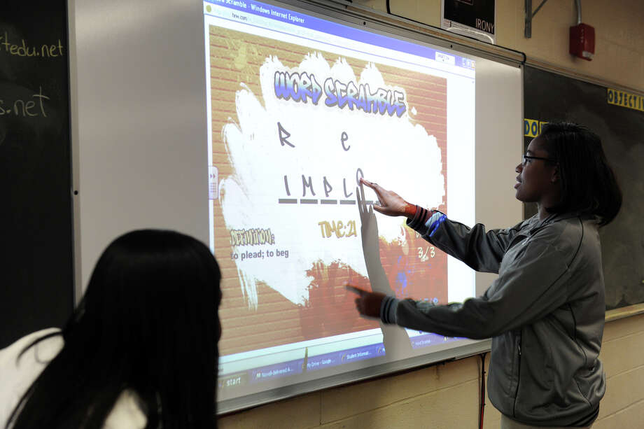 Shemeca Thompson works to complete a word scramble problem on a smart board in her Senior English class at Harding High School, in Bridgeport, Conn., Oct. 10, 2013. The interactive smart boards are one of the new paperless technologies being introduced into Bridgeport classrooms. Photo: Ned Gerard / Connecticut Post
