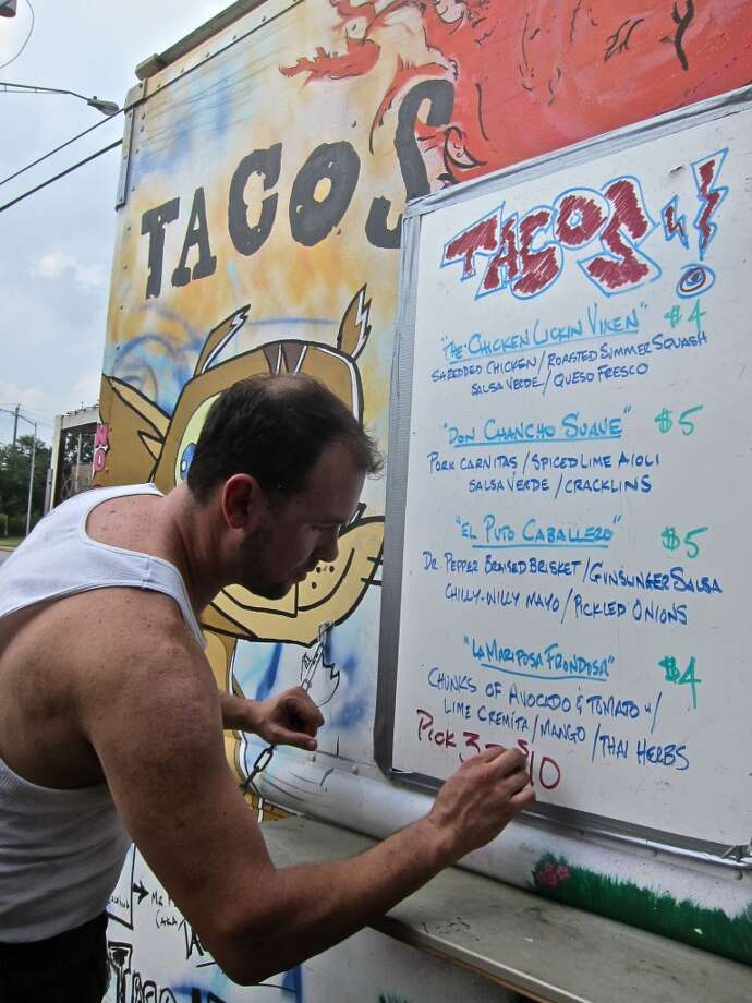 LJ Wiley puts the final touches on his daily menu at the Taco Nuts truck. Photo: Alison Cook