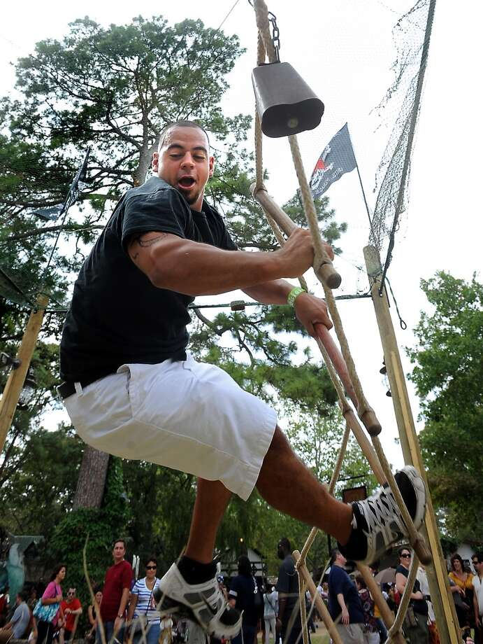 Geovanny Martinez falls off the rope ladder as he attempts to ring the cowbell on the Jacob's Ladder game at the Texas Renaissance Festival, Saturday, October 8, 2011. Tammy McKinley/The Enterprise Photo: Beaumont Enterprise