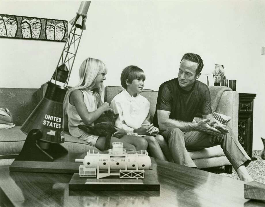 PHOTO FILED: MALCOLM SCOTT CARPENTER.   1967 - After announcement of his new Navy assignment, astronaut M. Scott Carpenter talks with his daughters, Kris and Candy, at their home near the Houston Manned Spacecraft Center. On the table are models of the Mercury spacecraft in which he orbited Earth three times in 1962 and Sealab II, in which he lived for 30 days 205 feet under the Pacific Ocean.  credit: c. 1967 World Book Encyclopedia Science Service, Inc. / Del Borer Photo: Del Borer, World Book Encyclopedia Science / handout
