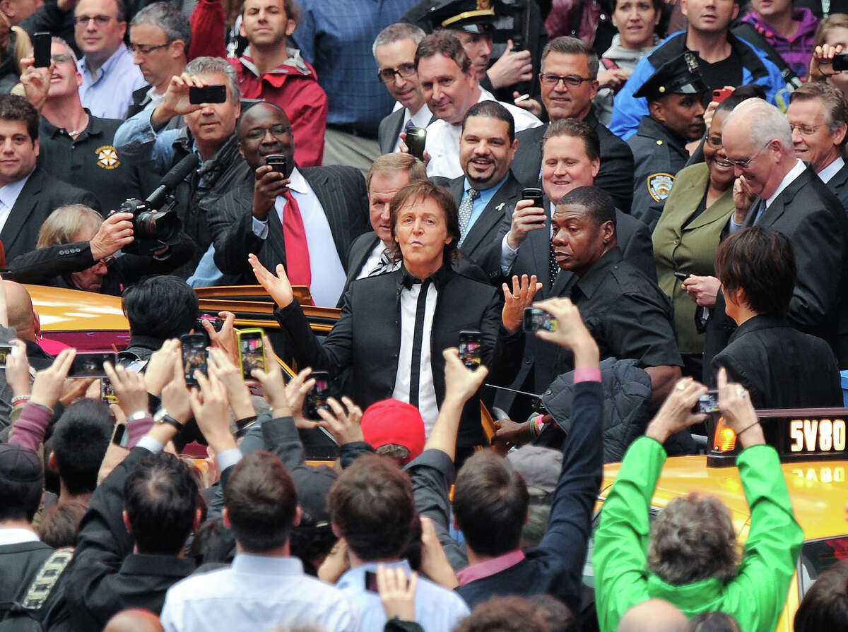 Paul McCartney arrives with his band to give a surprise pop up concert in Times Square on Thursday, Oct. 10, 2013 in New York. McCartney will release his new album called