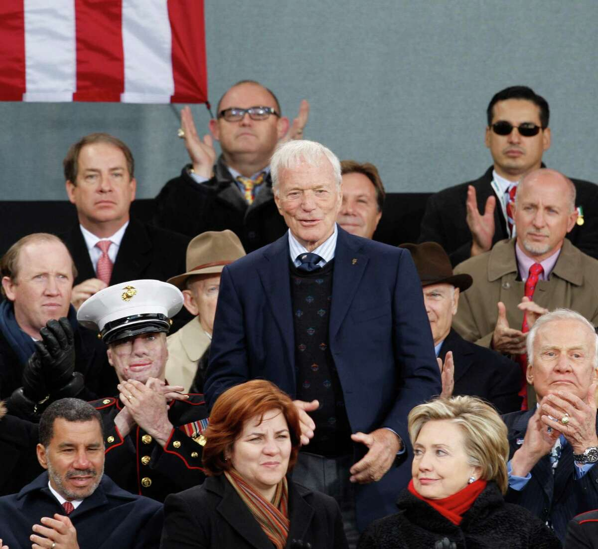 Dignitaries applaud as Astronaut Scott Carpenter, center, is introduced at the rededication ceremony for the Intrepid Sea, Air and Space Museum in New York, Tuesday, Nov. 11, 2008. New York Governor David Patterson, lower left, City Council Speaker Christine Quinn, lower row, center, and U.S. Senator Hillary Clinton, D-N.Y., are seated on the stage for the visit of President George Bush. (AP Photo/Kathy Willens)