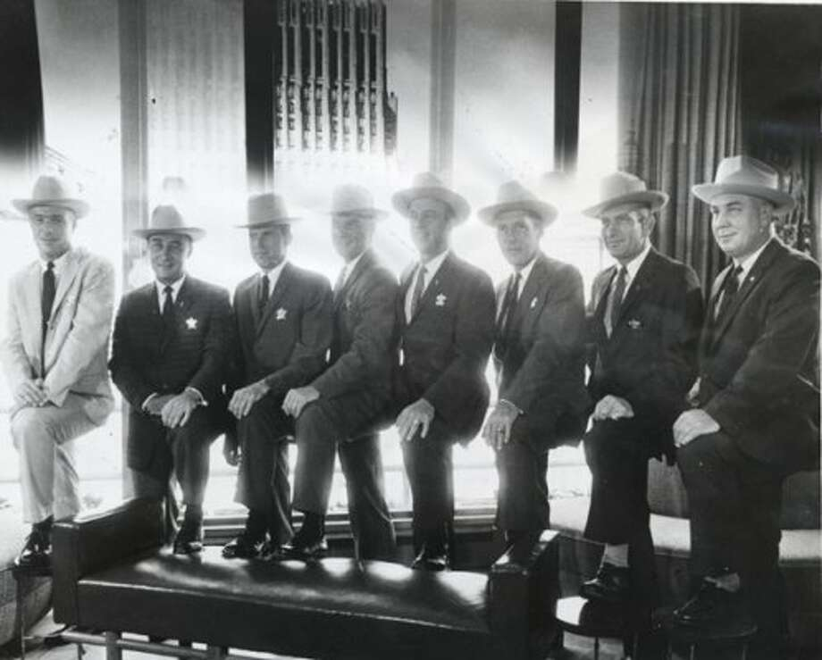 "This is the first picture of all seven astronauts in Houston. They're shown July 4, 1962, in the Petroleum Club, atop the Rice Hotel at Main and Texas. They are: astronauts Scott Carpenter, Virgil ""Gus"" Grissom, Gordon Cooper, John Glenn, Alan Shepard, Walter ""Wally"" Schirra, Donald ""Deke"" Slayton and Manned Spacecraft Center associate director Walter C. Williams. They were presented Western-style Stetson hats and gold honorary deputy badges. (Houston Chronicle)"