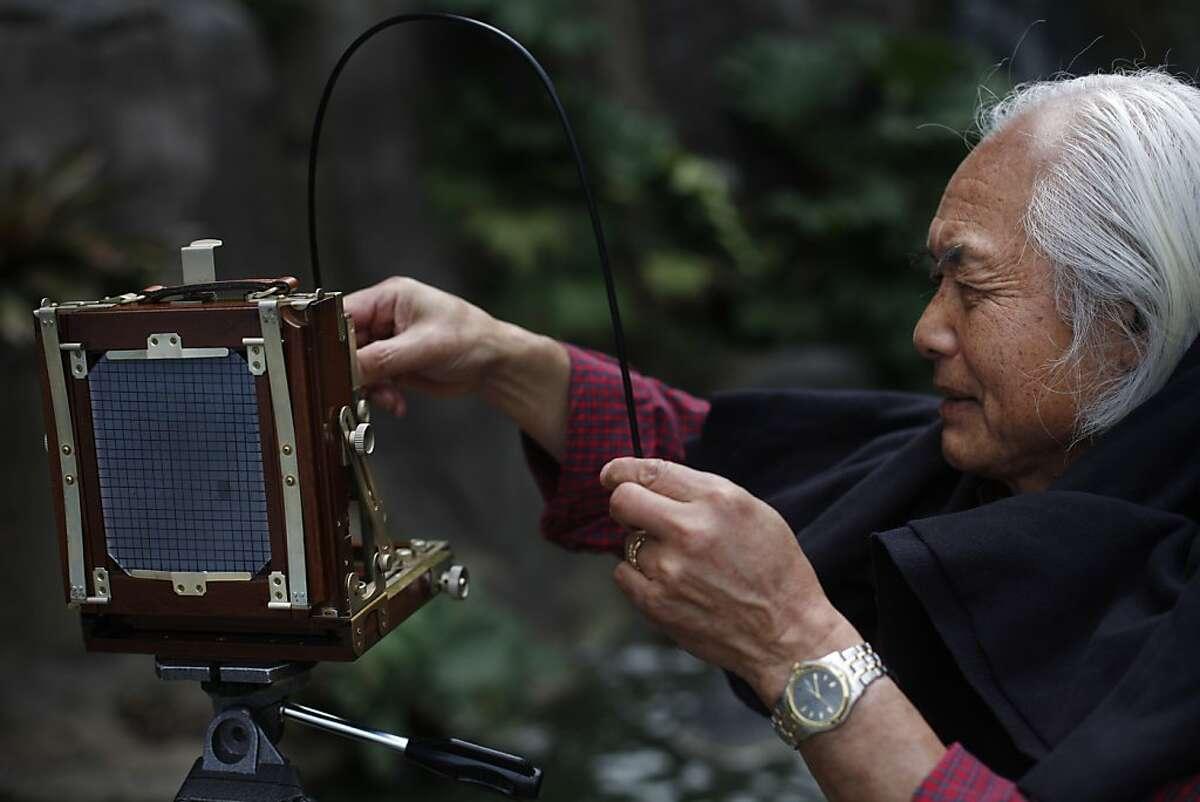 Photographer Mitsu Yoshikawa assembles his 4x5 field camera at Stow Lake on Monday, August 19, 2013 in San Francisco, Calif.