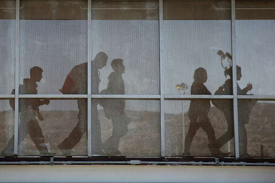 A group of immigrants walks into Mexico after being deported by U.S. immigration authorities. Many deportees are sent to danger zones where they become victims of cartels. Photo: John Moore, Getty Images / 2013 Getty Images