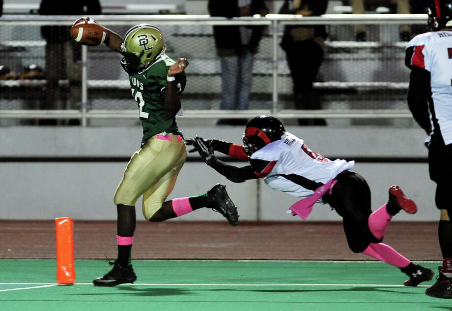 Bassick's Jihad Whitaker takes the ball into the endzone for a touchdown as Central's Manny Lavant fails to grab him, during high school football action in Bridgeport, Conn. on Thursday October 10, 2013. Photo: Christian Abraham / Connecticut Post