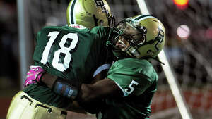 Bassick's Julian Fyffe, right, celebrates in the endzone after a touchdown by teammate Shavonne Brammwell, during high school football action against Central in Bridgeport, Conn. on Thursday October 10, 2013.