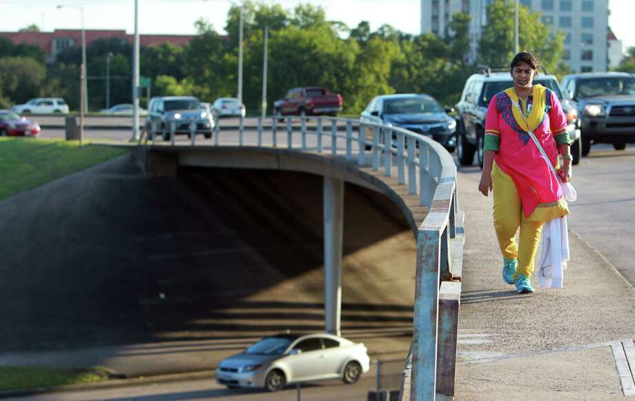 Despite her unease with vehicles passing so close by, Priyanka Gupta crosses the Waugh bridge Thursday over Memorial Drive. Photo: Mayra Beltran, Staff / © 2013 Houston Chronicle
