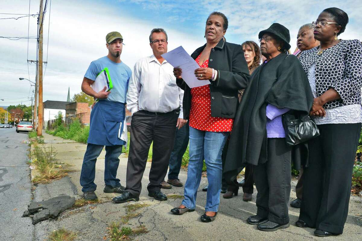 Hamilton Hill Neighborhood Association president, Marva Isaacs, center, is joined by residents and business owners as she speaks during a press Thursday, Oct. 10, 2013, conference to announce an initiative to clean up an Albany Street neighborhood in Schenectady, NY. (John Carl D'Annibale / Times Union)