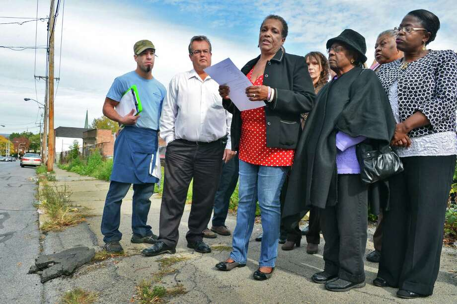 Hamilton Hill Neighborhood Association president,  Marva Isaacs, center, is joined by residents and business owners as she speaks during a press Thursday, Oct. 10, 2013, conference to announce an initiative to clean up an Albany Street neighborhood in Schenectady, NY. (John Carl D'Annibale / Times Union) Photo: John Carl D'Annibale / 00024199A