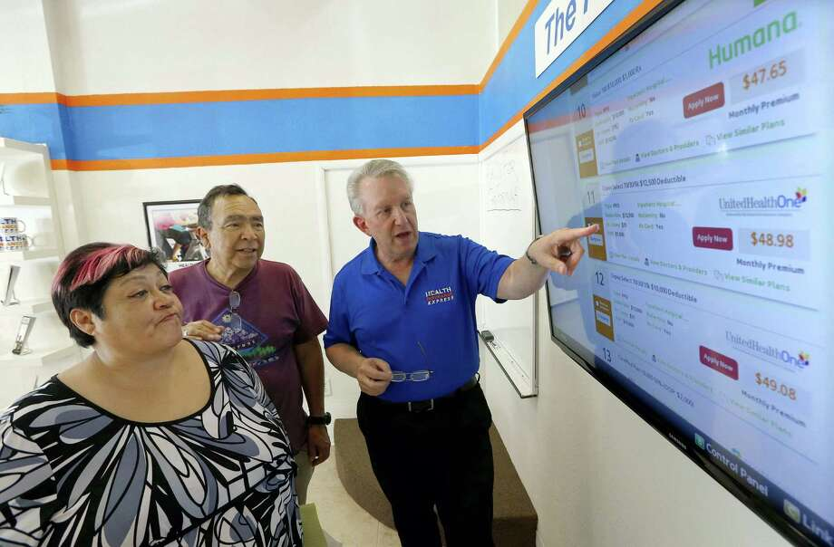 Alan Leafman (right), president of Health Insurance Express Inc., helps consumers navigate the nation's new health care insurance system online at the Health Insurance Express store in Mesa, Ariz. Photo: Ross D. Franklin / Associated Press