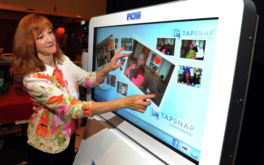 Patti McAuley show the abilities of the TapSnap touch screen computer at her home in Trumbull, Conn. on Thursday October 10, 2013. TapSnap is a new state-of-the-art phototainment system. The photos it takes can be immediately be uploaded to email, Facebook, or any other social media site. Photo: Christian Abraham / Connecticut Post