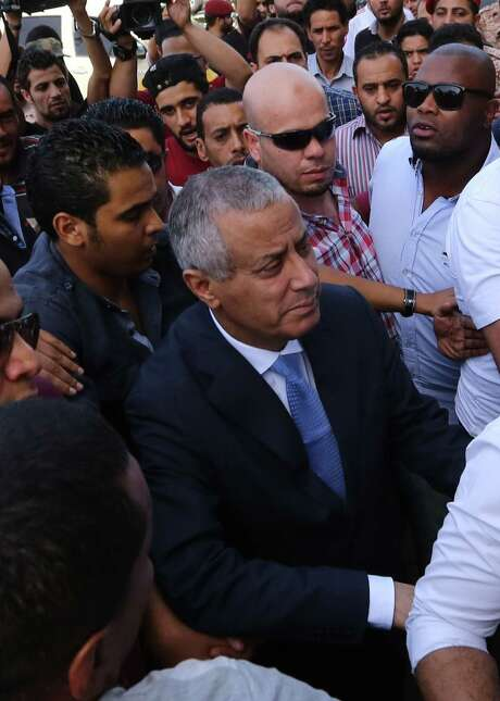 Libyan Prime Minister Ali Zeidan arrives at the government headquarters in Tripoli shortly after he was freed from the captivity of militiamen who had held him for several hours. The gunmen seized Zeidan from a hotel, where he resides in the Libyan capital. Photo: MAHMUD TURKIA / AFP/Getty Images