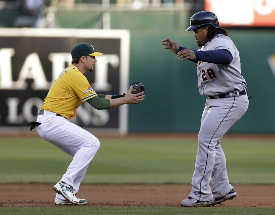 Oakland Athletics shortstop Jed Lowrie, left, tags out Detroit Tigers Prince Fielder in a rundown after a steal-attempt in the second inning of Game 5 of an AL baseball division series in Oakland, Calif., Thursday, Oct. 10, 2013. (AP Photo/Marcio Jose Sanchez) Photo: Associated Press