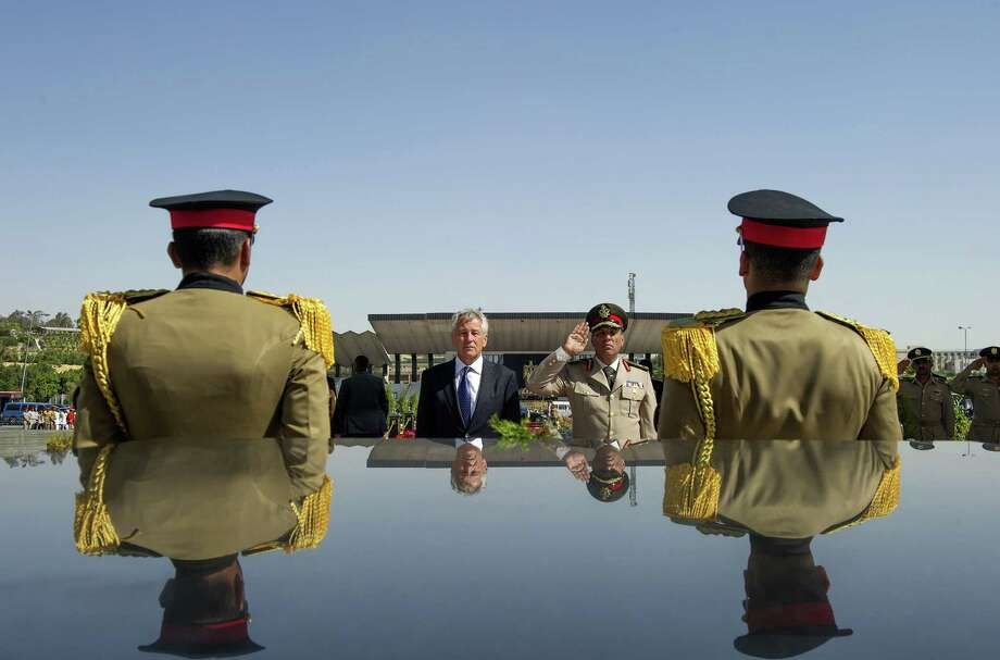 FILE - In this Wednesday, April 24, 2013, file photo, U.S. Secretary of Defense Chuck Hagel, second left, stands with an Egyptian army official before laying a wreath at the tomb of late President Anwar al-Sadat in Cairo. Washington's decision to withhold millions of dollars in mostly military aid to Egypt fuels anti-U.S. sentiment in the most populous Arab nation along with the perception that Washington supports Morsi, the Islamist president the military ousted in a July coup. Heightening those sentiments could boost the popularity of Gen. Abdel-Fattah el-Sissi, whom the U.S. is trying to pressure to ensure a transition to democracy. (AP Photo/Jim Watson, Pool, File) ORG XMIT: NY121 Photo: Jim Watson / Pool AFP