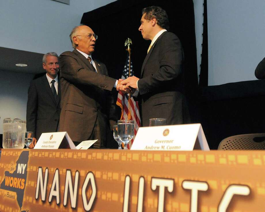 Hector Ruiz, left, chairman and CEO of Advanced Nanotechnology Solutions, Inc. and Gov. Andrew Cuomo meet Thursday, Oct. 10, 2013, in Utica, N.Y., following the announcement of Nano Utica. The consortium consists a group of more than six leading tech companies and will include a $1.5 billion investment. (Mark DiOrio / Observer-Dispatch) ORG XMIT: NYUTI Photo: Mark DiOrio / ©2013