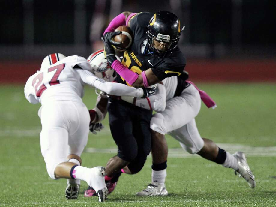 Klein Oak's Derrick Durden center, is tackled by Atascocita defenders during the first quarter of high school football game action at Klein Memorial Stadium Thursday, Oct. 10, 2013, in Houston. Photo: James Nielsen, Houston Chronicle / © 2013  Houston Chronicle
