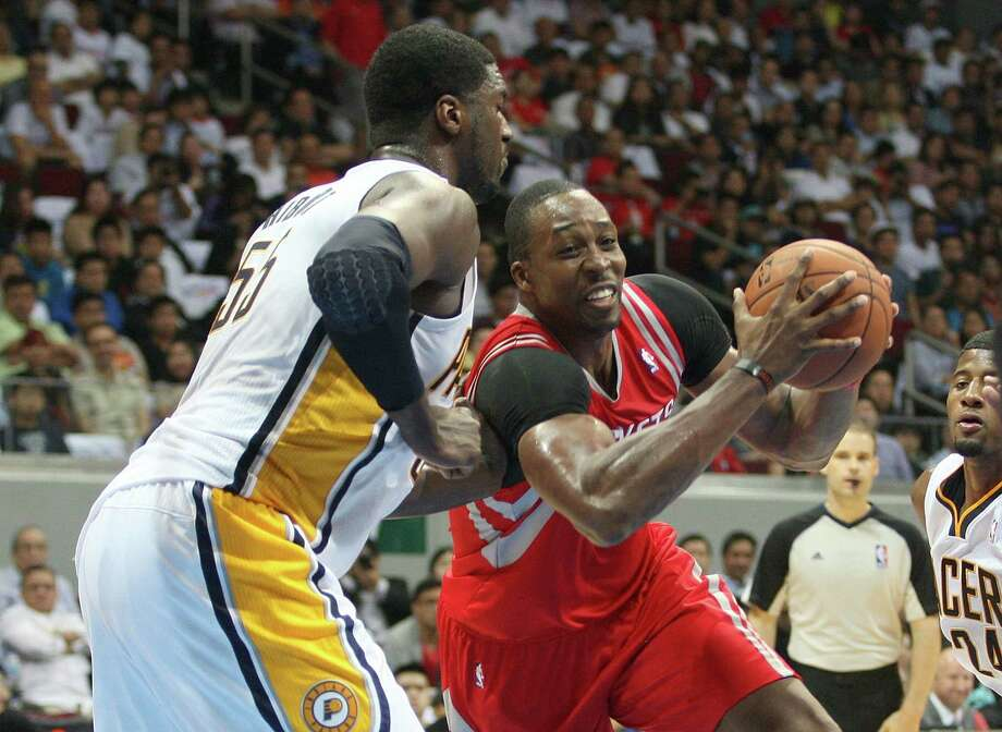 Houston's Dwight Howard (right), making a move against Indiana's Roy Hibbert, struggled with foul trouble in the Rockets' 116-96 victory. Photo: Mike Young / Getty Images