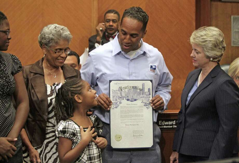 "Chinyere Thompson, 15, her sister, Asia Thompson, 7, their grandmother, Dedriel Thompson, their dad, U.S. Postal Service employee Danny Thompson and City of Houston Mayor Annise Parker, right, line up to pose for photos after a proclamation declaring ""Danny Thompson Day"" during City Council's weekly meeting in the Council Chamber Tuesday, Aug. 7, 2012, in Houston. Thompson saved two children from a burning home while on his route. Photo: Melissa Phillip / Houston Chronicle"
