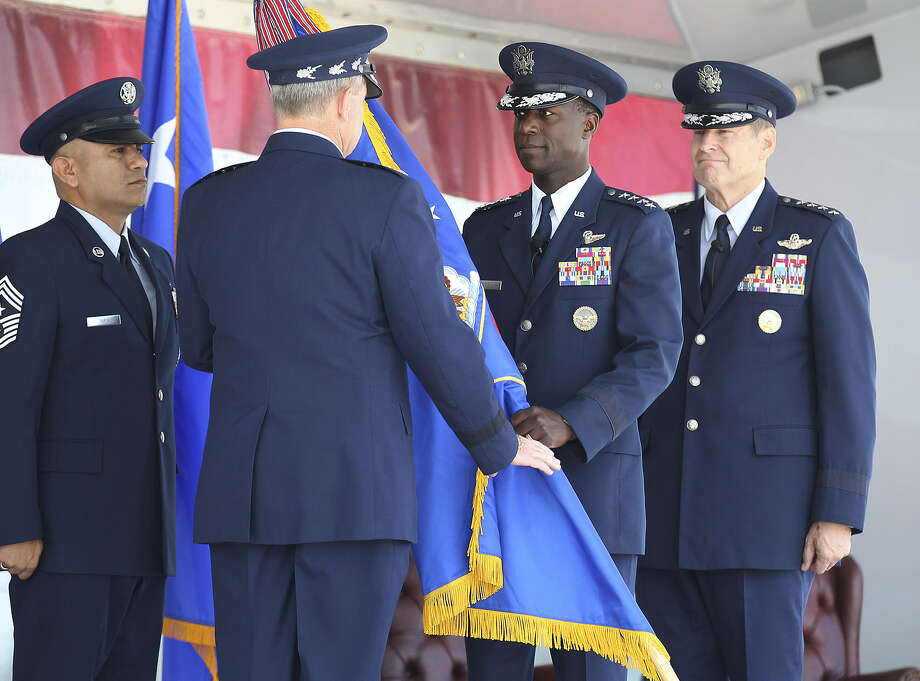 Gen. Edward Rice, Jr. (center, facing camera), 57, relinquishes the command flag to Gen. Mark Welsh, chief of staff of the Air Force, as Gen. Robin Rand waits to accept the banner. Photo: Photos By Kin Man Hui / San Antonio Express-News