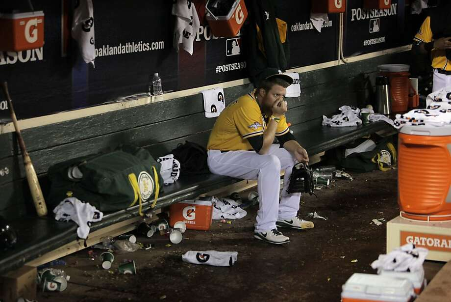 Sean Doolittle sits forlornly in the A's dugout after Oakland's second consecutive postseason appearance ended with a first-round playoff loss to the Tigers. Photo: Carlos Avila Gonzalez, The Chronicle