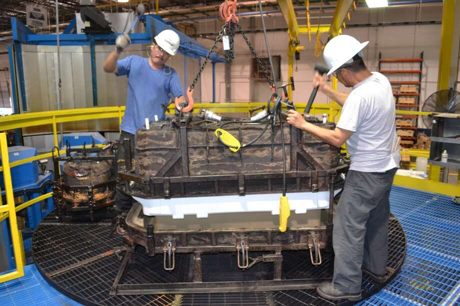 Igloo plant workers Carlos Gutierrez, left, and Julian Maradiaga remove a new Yukon 250 cooler from a rotational-molding machine at the Igloo plant in Katy. Photo: Ronnie Crocker, Houston Chronicle