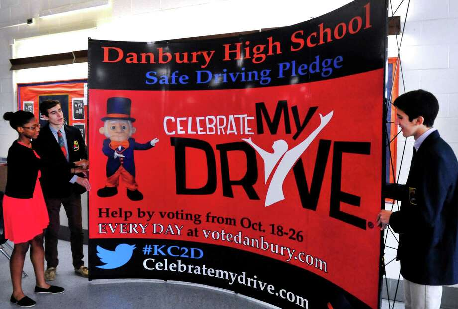 Najmah James, left, Chazz Winter, and Dan Maffucci, right, Danbury High School senior class student leaders, move a display promoting their citywide project to have people pledge that they won't text and drive, during a meeting at the school Friday, Oct. 11, 2013. If the school gets the most pledges in the contest run by State Farm Insurance, it would win $100,000 and an appearance by singer Kelly Clarkson. Photo: Michael Duffy / The News-Times