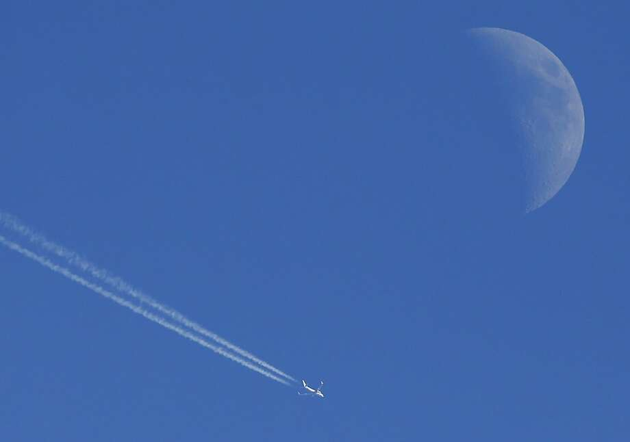 A jet soars by the moon over Lawrence, Kan. Photo: Orlin Wagner, Associated Press