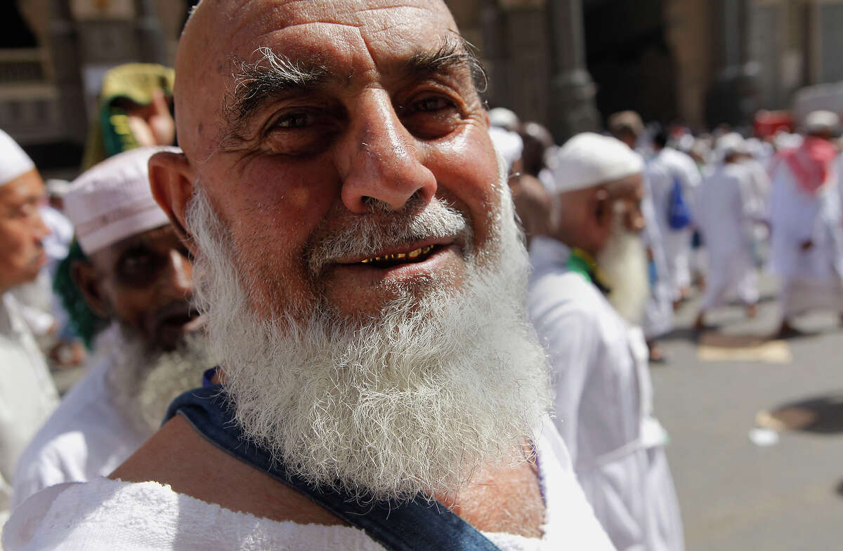 Mohammed Akhmetov, 71, a Muslim pilgrim from Kazakhstan who is performing the hajj for the first time, poses for a photograph as he leaves the Grand Mosque in the Muslim holy city of Mecca, Saudi Arabia, Friday, Oct. 11, 2013. Every Muslim is required to perform the hajj, or pilgrimage, to Mecca at least once in his or her lifetime if able to do so. (AP Photo/Amr Nabil)