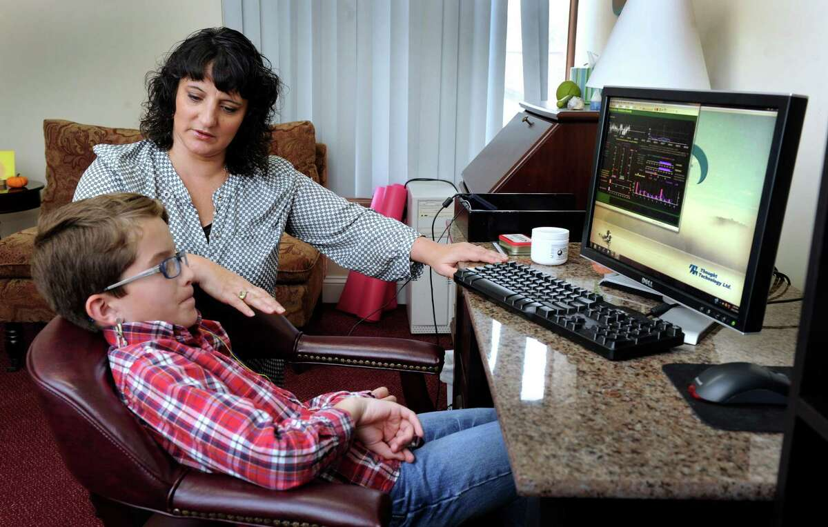 Roseann Capanna-Hodge, and educational psychologist consultant neurofeedback practitioner, works with Drew Cousens, 10, of Bethel, Friday, Oct. 11, 2013 in her Ridgefield, Conn. office.