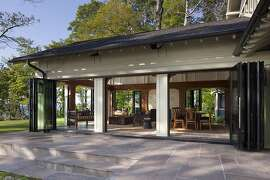 NanaWall's sliding glass walls enable this dining room to open to the forest on all sides.
