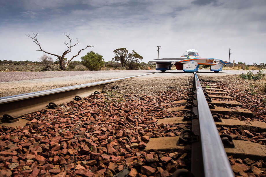 In this picture taken on Thursday Oct. 10, 2013 the Indupol One of the Belgian Solar Team crosses a railway over the Stuart Highway 50km South of Fort Augusta, Australia, during the 2013 World Solar Challenge. The race, lasting for seven days, takes 43 participants over 3,021 kilometers before ending on Sunday, Oct 13. Photo: Geert Vanden Wijngaert, AP / AP