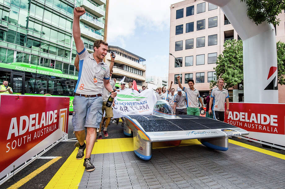 Belgian Solar Team members and their car, the Indupol One, pass the finish line of the 2013 World Solar Challenge in Adelaide, Australia, on Friday Oct. 11, 2013. The race, lasting for seven days, takes 43 participants over 3,021 kilometers before ending on Sunday, Oct 13. The Belgian team finished 6th. Photo: Geert Vanden Wijngaert, AP / AP